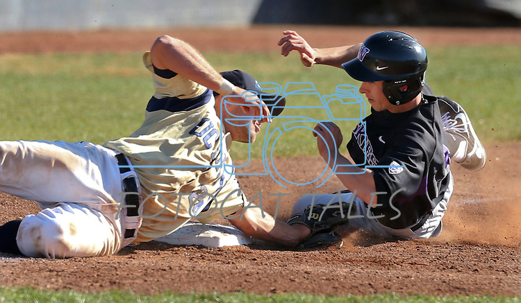 UC Davis third baseman Paul Politi tries to make a diving tag on University of Washington's Ty Afenir in a college baseball game between the  and the UC Davis Aggies in Davis, Ca., on Sunday, Feb. 17, 2013. Davis won 7-5 to finish their season opening series 3-1. .Photo by Cathleen Allison