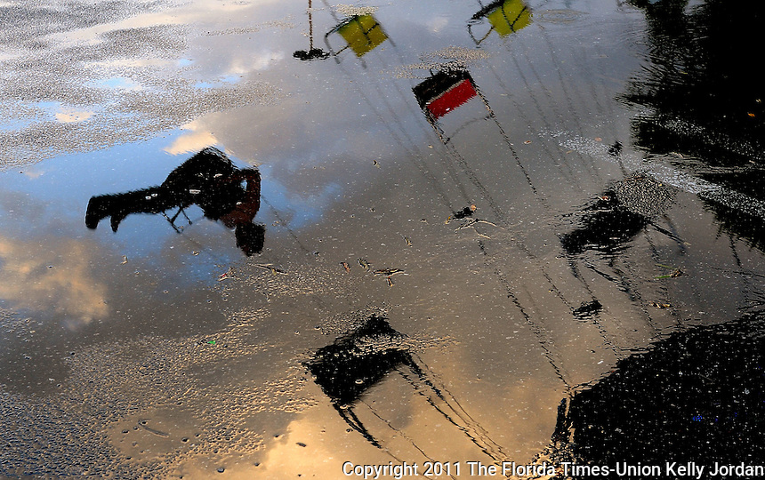 Kelly.Jordan@jacksonville.com--100611--A person riding the swing ride is reflected in a puddle at a carnival in the parking lot of the Orange Park Mall late Thursday afternoon, October 6, 2011. Heavy rains moving through the area made for a soggy afternoon for carnival goers. The carnival, featuring Hildebrand Carnival rides will be open through Sunday October 9, 2011. The gates open at 5 p.m. daily and noon on the weekend.(The Florida Times-Union, Kelly Jordan)