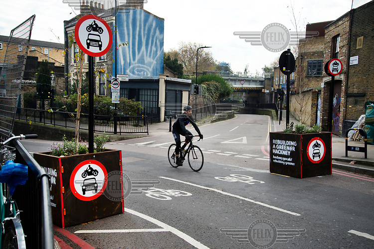 A bicyclist passes through the entrance to a no-car zone on Middleton Road in Hackney.