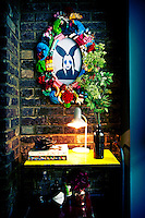 A fun photo inside a funky picture frame hangs on a brick wall. An arrangement of green flowers in a black vase and a lit desk lamp stand on a yellow trolley.