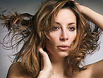 Beauty portrait of a woman with flying light brown hair and natural makeup in her early thirties on gray background Image © MaximImages, License at https://www.maximimages.com