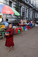 Myanmar, Burma, Yangon.  Young Buddhist Monk with Begging Bowl for Food Donations.