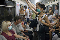 Moscow, Russia, 06/08/2010. .Travellers on the Moscow metro wear protective masks against the intense smog that has permeated every part of he city in the record high temperatures of the continuing heatwave. Peat and forest fires in the countryside surrounding Moscow have resulted in the Russian capital being blanketed in heavy smog.