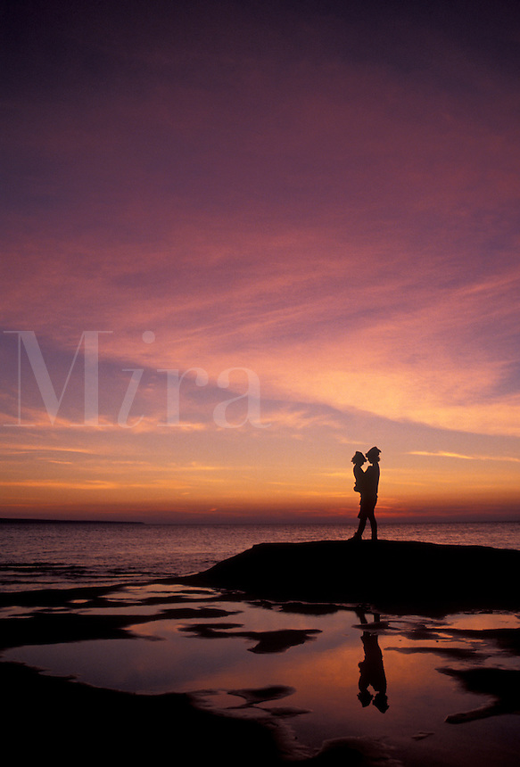 AJ2825, sunset, sunrise, silhouette, Lake Superior, Pictured Rocks, Upper Peninsula, U.P., Michigan, Mother and daughter standing on the edge of Lake Superior at sunset at Pictured Rocks National Lakeshore in Munising in the state of Michigan.