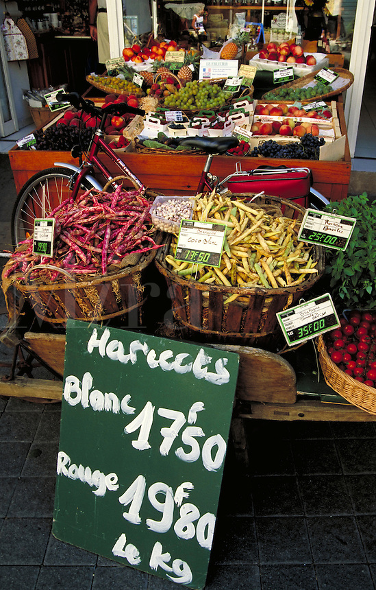 Colorful produce in trays and baskets displayed with prices outside Le Fruitier shop. Shiny woman's bicycle leans against one table; hand-lettered green sign leans against another. L'Isle sur, la Sorgue Provence France.