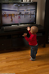 18 month old toddler boy standing close to television set watching cartoon, clapping hands to music