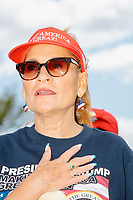 """A woman wears a Trump campaign shirt and hat while reciting the Pledge of Allegiance as people gather for an anti-lockdown protest organized by the alt-right group Super Happy Fun America near the home of Massachusetts governor Charlie Baker in Swampscott, Massachusetts, on Sat., May 16, 2020. The protest was in defiance of Massachusetts orders mandating face coverings and social distancing and prohibiting gatherings larger than 10 people during the ongoing Coronavirus (COVID-19) global pandemic. The state's stay-at-home order is expected to be updated on May 18, 2020, with a phased reopening plan issued by the governor as COVID-19 cases continue to decrease. Anti-lockdown protests such as this have become a conservative cause and have been celebrated by US president Donald Trump. Many of the protestors displayed pro-Trump messages or wore Trump campaign hats and shirts with phrases including """"Trump 2020"""" and """"Keep America Great."""" Super Happy Fun America, organizers of the protest, are an alt-right organization best known for creating the 2019 Boston Straight Pride Parade."""