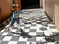 """Gaza.June.09.2008.Aya Masouad 8 years born without arms,use here toes and feet to go around with her daily life,she payling with her sister in her house. she easts or drink with her toes , she love her life and thanking God, she practice her life as she is normel people . """" Photo by Fady Adwan/propaimages"""""""