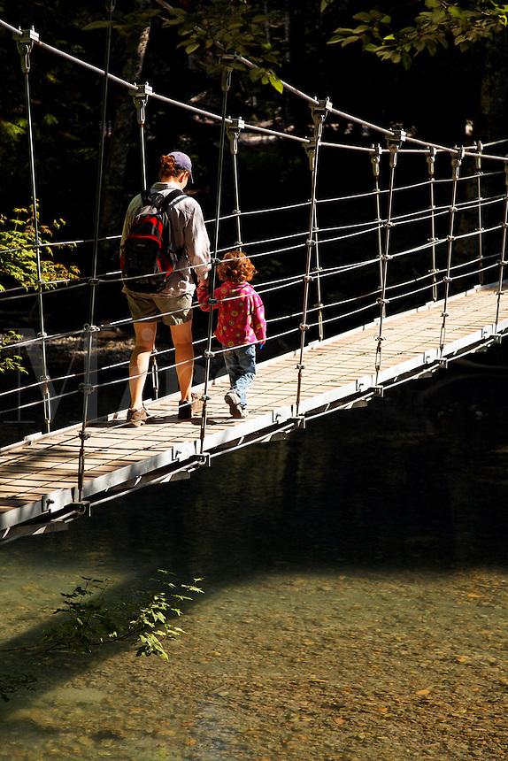 Mother and daughter crossing suspension bridge over Ohanapecosh River, Grove of the Patriarchs Trail, Mount Rainier National Park, Washington, USA