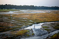 A man walks across a flat landscape next to the Mechi bridge which connects India and Nepal near the Panitanki border post. The border point is one of the main smuggling routes for tiger parts trafficking between India and China.