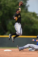 Pittsburgh Pirates Tyler Filliben (66) jumps for a high throw as Matt Dean (25) slides in during a minor league spring training game against the Toronto Blue Jays on March 26, 2015 at Pirate City in Bradenton, Florida.  (Mike Janes/Four Seam Images)