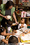 Preschool Headstart 3-5 year olds children doing guided observation and drawing comparing eggs from different mammals female teacher talking to group of students