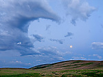 Clouds in the shape of Bakunawa, a moon-eating dragon, form over the Zumwalt Prairie in northeastern Oregon, USA