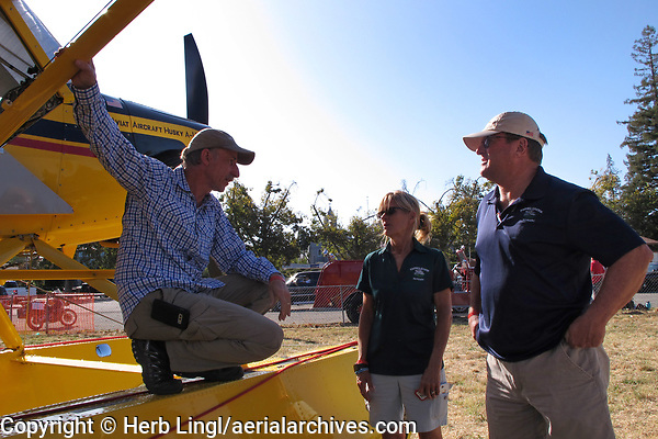 Certified flilght instructor Terry Hayes of Foothill Aviation and her husband Mike speak with Doug Lumgair, owner of N176WW, an Aviat Aircraft Husky A-1B at the Clear Lake Seaplane Splash-In, Lakeport, Lake County, California