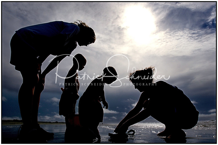Two women interact with their children during a family vacation to the beach near Charleston, SC.  Model released image may be used to illustrate other destinations or concepts.