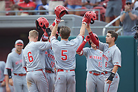 Patrick Bailey (5) of the North Carolina State Wolfpack is greeted at home plate by teammates Will Wilson (8) and Brett Kinneman (6) after hitting his second home run of the game against the Northeastern Huskies at Doak Field at Dail Park on June 2, 2018 in Raleigh, North Carolina. The Wolfpack defeated the Huskies 9-2. (Brian Westerholt/Four Seam Images)
