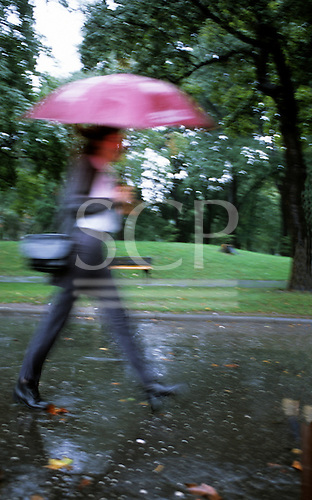 Belgrade, Serbia, Yugoslavia. Fashionable young woman in the rain with an umbrella marching through a park; blurred movement.