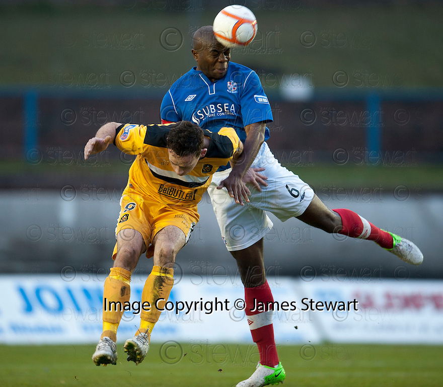 Cowdenbeath's Joe Mbu clears from Dumbarton's Jim Lister  ...