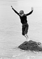 Leaping from a rock.  One of the kids from Wester Hailes on a visit with Youth Workers to the beach near Dunbar, East Lothian, Scotland, 1979.  John Walmsley was Photographer in Residence at the Education Centre for three weeks in 1979.  The Education Centre was, at the time, Scotland's largest purpose built community High School open all day every day for all ages from primary to adults.  The town of Wester Hailes, a few miles to the south west of Edinburgh, was built in the early 1970s mostly of blocks of flats and high rises.