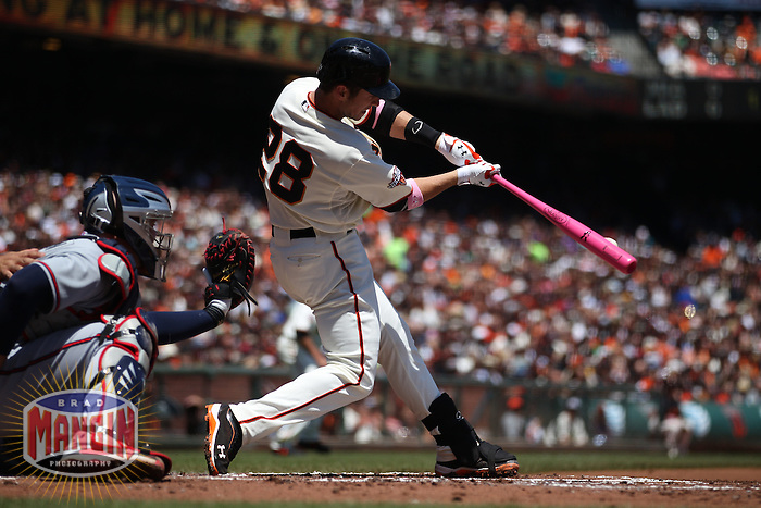 SAN FRANCISCO, CA - MAY 12:  Buster Posey #28 of the San Francisco Giants bats using a pink bat in honor of Mother's Day and breast cancer awareness against the Atlanta Braves during the game at AT&T Park on Sunday, May 12, 2013 in San Francisco, California. Photo by Brad Mangin