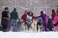 Silvia Furtwangler gives high-fives to spectators along the trail during the Ceremonial Start of Iditarod 2012 in Anchorage, Alaska.