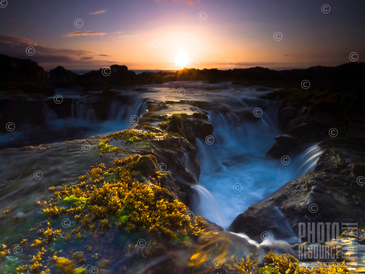 At sunset, waves pour into the large holes along the Keahole Point's rocky coastline, Big Island.