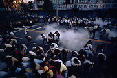 """Chunju, South Korea<br /> May 1986<br /> <br /> A peaceful opposition rally is dispersed by riot police with CS tear gas.<br /> <br /> After two decades of building an economic miracle, in the summer of 1987 tens of thousands of frustrated South Korean students took to the streets demanding democratic reform. """"People Power"""" Korean-style saw Koreans from all social spectrums join in the protests...With the Olympics to be held in South Korea in 1988, President Chun Doo Hwan decided on no political reforms and to choose the ruling party chairman, Roh Tae Woo, as his heir. The protests multiplied and after 3 weeks Chun conceded releasing oppositionist Kim Dae Jung from his 55th house arrest and shaking hands with opposition leader Kim Young Sam. Days later he endorsed presidential elections and an amnesty for nearly 3,000 political prisoners. It marked the first genuine initiative of democratic reform in South Korea and the people had their victory."""