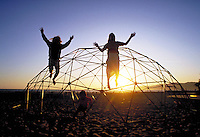 TWO CHILDREN JUMPING OFF PLAYSCAPE ON BEACH AT SUNSET. TWO CHILDREN. OAKLAND CALIFORNIA.