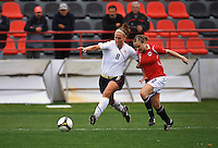 Lauren Cheney stretches for the ball while being held by a Norwegian defender. The USA defeated Norway 2-1 at Olhao Stadium on February 26, 2010 at the Algarve Cup.