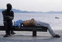 Man sleeps beside Brazilian poet Carlos Drummond de Andrade statue at Copacabana beach sidewalk, Rio de Janeiro, Brazil.