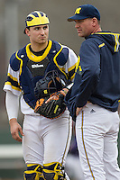 Michigan Wolverines catcher Harrison Wenson (45) talks with coach Sean Kenny during the NCAA baseball game against the Washington Huskies on February 16, 2014 at Bobcat Ballpark in San Marcos, Texas. The game went eight innings, before travel curfew ended the contest in a 7-7 tie. (Andrew Woolley/Four Seam Images)