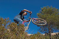 Man making jumps through bushes on his mountain bike, Vitrolles, Provence, France.