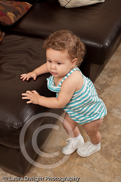 13 month old baby girl at home standing and walking with support of couch vertical