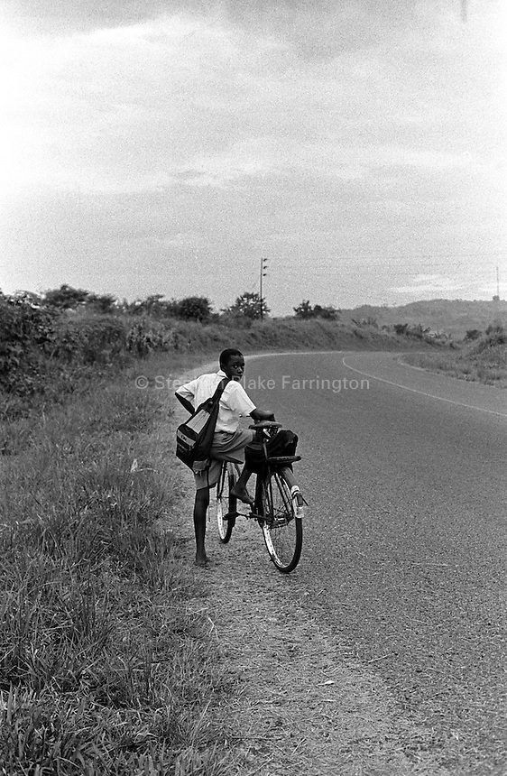 A student returning home at the end of the day. Uganda has an estimated 1.5 million people infected with HIV/AIDS and contains over 1 million orphans many of which cannot afford education. Mbiko, Mokono District, Uganda, Africa. June 2004 © Stephen Blake Farrington