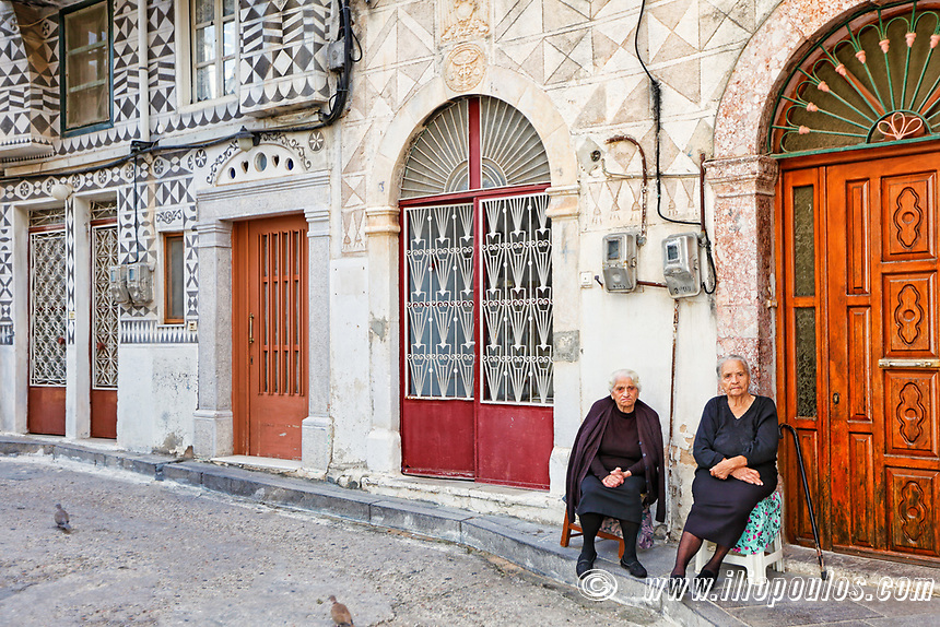 Old women outside traditional houses decorated with the famous geometric scratch patterns in the medieval mastic village of Pyrgi on the island of Chios, Greece
