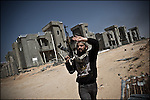© Remi OCHLIK/IP3 - Bin Jawwad March 28, 2011 -- A fighter come back from checking the empty bulding looking for Qadhafi s mercenaries...Rebel forces bore down Monday on Moammar Gadhafi's hometown of Sirte, a key government stronghold where a brigade headed by one of the Libyan leader's sons was digging in to defend the city and setting the stage for a bloody and possibly decisive battle. The opposition made new headway in its rapid advance westward through oil towns and along stretches of empty desert highway toward Sirte and beyond to the big prize -- the capital, Tripoli. Rebels attack had been stopped 50 kilos from Syrte