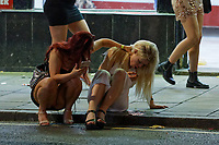 Pictured: Two young women sit on the pavement in Swansea. Tuesday 31 December 2019 to Wednesday 01 January 2020<br /> Re: Revellers on a night out for New Year's Eve in Wind Street, Swansea, Wales, UK.