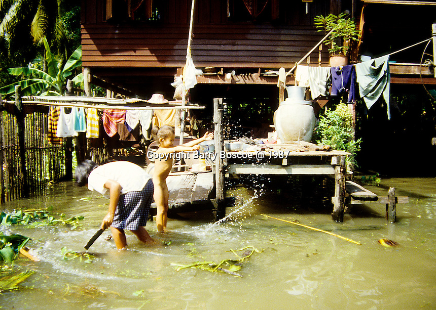 A child and her Mother playing and working in their front yard near Bangkok, Thailand