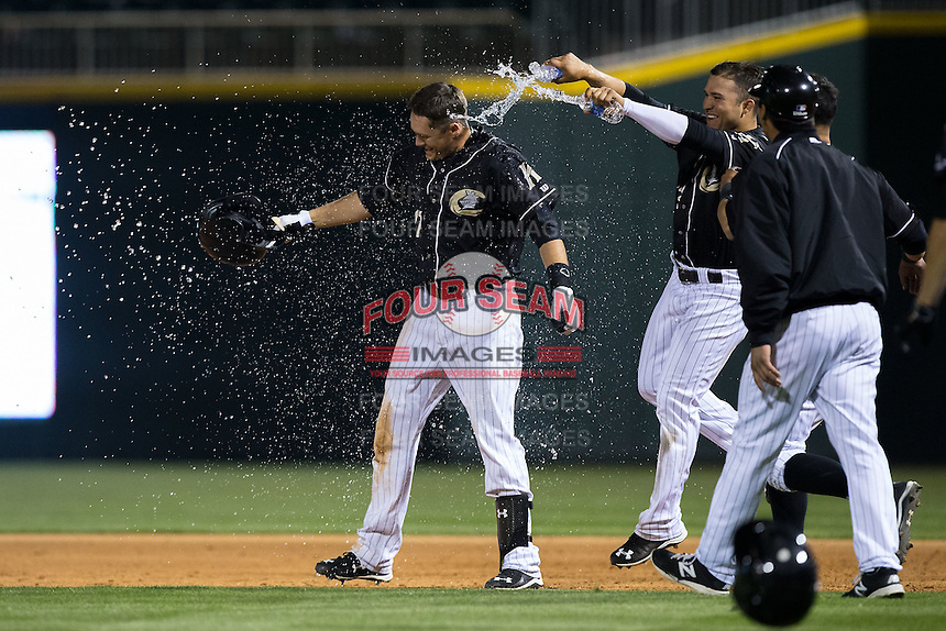 Jason Coats (17) of the Charlotte Knights is doused with water by teammate Carlos Sanchez (13) after hitting a walk-off single to defeat the Toledo Mud Hens at BB&T BallPark on April 27, 2015 in Charlotte, North Carolina.  The Knights defeated the Mud Hens 7-6 in 10 innings.   (Brian Westerholt/Four Seam Images)