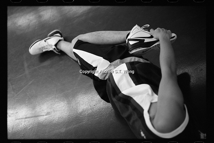 A basketball player of Dongguan Guangming Middle School in Dongguan, Guangdong province, stretches during a training session, November 2011.