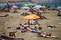 People sunbathing and bathing into the atlantic sea at Maspalomas beach