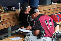 Wisconsin Timber Rattlers pitching coach Gary Lucas (25) goes over notes with catcher Natanael Mejia (14) before the first game of a doubleheader against the Quad Cities River Bandits on August 19, 2015 at Modern Woodmen Park in Davenport, Iowa.  Quad Cities defeated Wisconsin 3-2.  (Mike Janes/Four Seam Images)