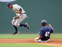 Second baseman Emerson Landoni (12) of the Charleston RiverDogs hops to get out of the way after forcing out Reynaldo Rodriguez (47) of the Greenville Drive in a game on Aug. 24, 2010, at Fluor Field at the West End in Greenville, S.C. Photo by: Tom Priddy/Four Seam Images
