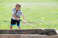 Eli Eagle, 9, uses a hoe Monday July 19, 2021 while working with other children to make garden beds during the Lifesource Summer Program. The project is spearheaded by program director Betty Metcalf. Metcalf also teaches at Butterfield Elementary School in Fayetteville and manages a garden project there. Visit nwaonline.com/21000720Daily/ and nwadg.com/photo. (NWA Democrat-Gazette/J.T. Wampler)
