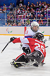 Sochi, RUSSIA - Mar 15 2014 - Graeme Murray takes a hit as Canada takes on Norway in the Bronze Medal Sledge Hockey game at Canada Paralympic House at the 2014 Paralympic Winter Games in Sochi, Russia.  (Photo: Matthew Murnaghan/Canadian Paralympic Committee)