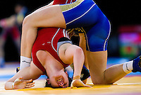 11 DEC 2011 - LONDON, GBR - Chloe Spiteri (GBR) (in red) attempts to avoid being pinned by Ekaterina Bukina (RUS) (in blue) during their 72kg category quarter final bout at the London International Wrestling Invitational and 2012 Olympic Games test event at the ExCel Exhibition Centre in London, Great Britain .(PHOTO (C) NIGEL FARROW)
