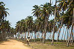 """A man selling cloth """"pagnes,"""" used as skirts for women carries a stack of neatly folded pagnes on his head, as he walks the road connecting Cotonou and the historic town of Ouidah."""