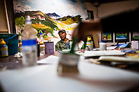 Kama Wangdi, 50, poses in front of his paintings commissioned by the Smithsonian Gallery in Washington. Kama runs VAST (Voluntary Artist Studio) and supports and mentors the young artists in Thimphu, Bhutan.