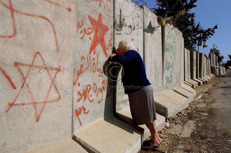 A Palestinian woman talks to people from other side of the wall built to separate the Palestinian territories from Israel, June 1,2003, in the West Bank neighbourhood of Abu Dis, next to Jerusalem. Photo by Quique Kierszenbaum