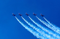 The Blue Angels FA 18s fly in tight formation with trails of white smoke against a clear blue sky